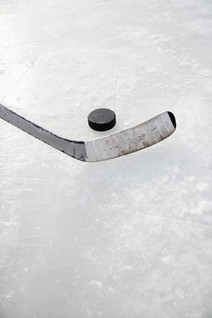 equipment: Close up of ice hockey stick on ice rink in position to hit hockey puck.