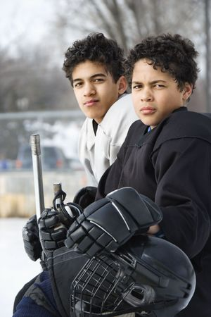 pre teen boys: Two boys in ice hockey uniforms sitting on ice rink sidelines looking. Stock Photo
