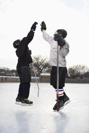 hockey sobre hielo: Dos ni�os en el hockey sobre hielo uniformes entre s� dando de alta cinco en pista de hielo.