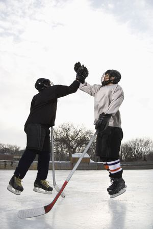 eachother: Two boys in ice hockey uniforms giving eachother high five on ice rink.