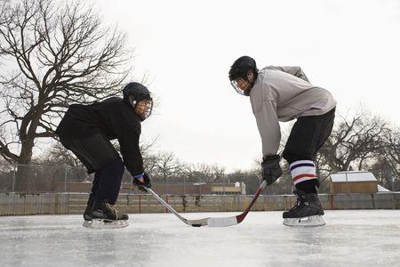 pre teen boys: Two ice hockey player boys in uniform facing off on ice.