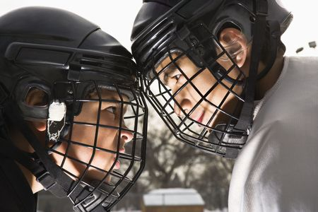 Two ice hockey players in uniform facing off trying to intimidate eachother.