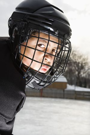 intimidating: Ice hockey player boy in uniform and cage helmet making mean face.