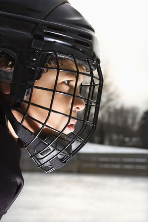Ice hockey player boy in uniform and cage helmet concentrating. photo
