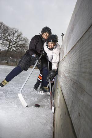 hockey sobre hielo: Jugador de hockey sobre hielo muchacho pirateo otro jugador en la pared tratando de llegar al tejo.