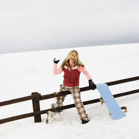 Young woman in winter clothes by fence in snowy field smiling while ready to throw snowball. photo