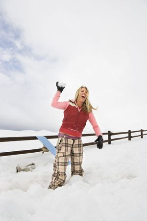 Young woman in winter clothes by fence in snowy field laughing and ready to throw snowball. photo