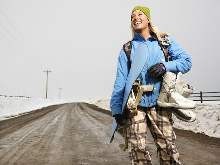 Young woman in winter clothes standing on muddy dirt road holding snowboard and boots smiling. photo