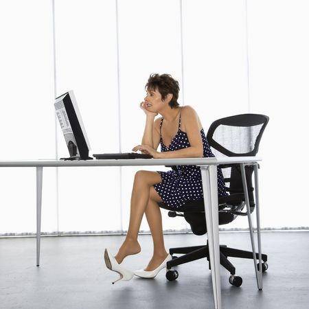Caucasian businesswoman sitting at desk with computer in office. photo