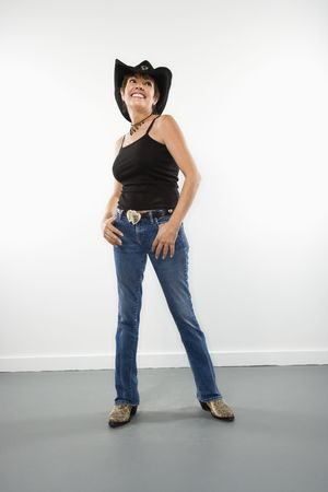 Full length portrait of pretty Caucasian woman smiling in cowgirl clothes. photo