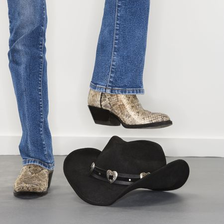 Woman wearing snakeskin cowboy boots holding foot as if to stomp on black cowboy hat. photo