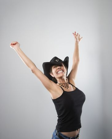 Portrait of woman smiling and holding arms up in air. photo