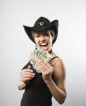 Woman making facial expression and holding twenty dollar bills in hand. photo