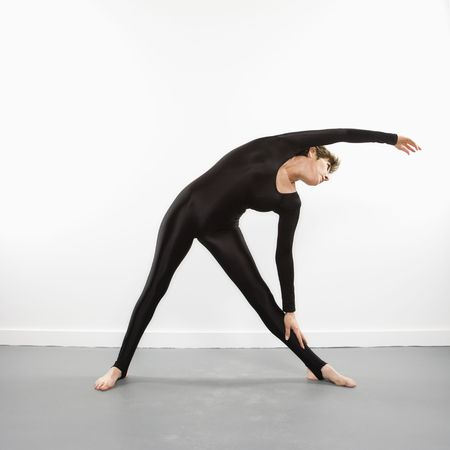 spandex: Portrait of pretty Caucasian woman in spandex bodysuit leaning and stretching to side. Stock Photo