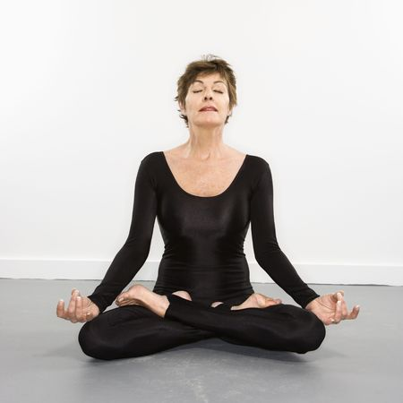 spandex: Portrait of pretty Caucasian woman in spandex bodysuit sitting in meditation lotus pose.