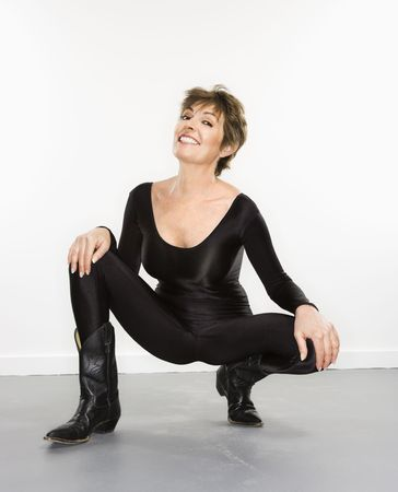 spandex: Portrait of pretty Caucasian woman in spandex bodysuit and black cowboy boots smiling. Stock Photo