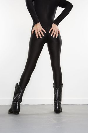 spandex: Back view portrait of pretty Caucasian woman in spandex bodysuit and black cowboy boots standing with hands on buttocks.