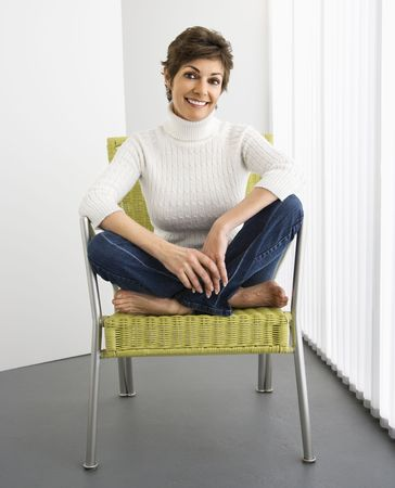 Portrait of pretty woman smiling sitting on modern chair. Stock Photo - 2044297