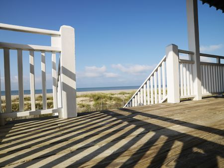 bald head island: View of beach from porch with railing casting shadow on wooden deck at Bald Head Island, North Carolina Stock Photo