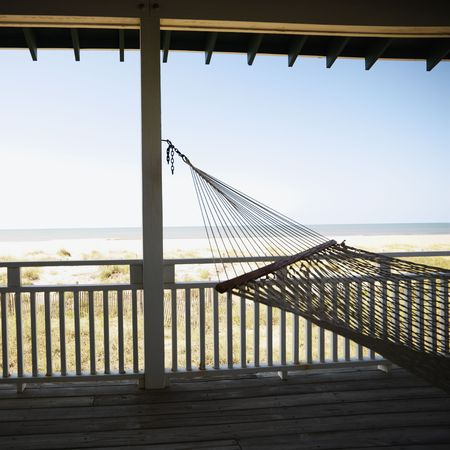 bald head island: View of beach from porch with railing and hammock at Bald Head Island, North Carolina