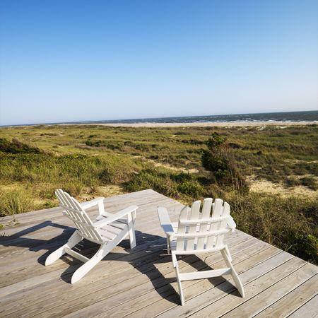 bald head island: Two adirondack chairs on wooden deck overlooking beach at Bald Head Island, North Carolina.