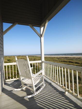 silla de madera: Mecedora de porche con vistas a la playa barandilla en Bald Head Island, Carolina del Norte.