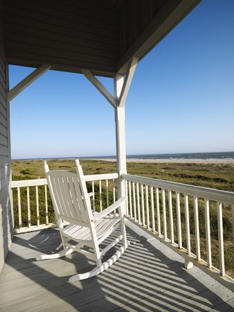 Rocking chair on porch with railing overlooking beach at Bald Head Island, North Carolina. Stock Photo