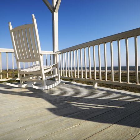 beach chairs: Rocking chair on porch with railing overlooking beach at Bald Head Island, North Carolina. Stock Photo
