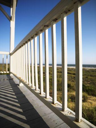 bald head island: Detail of wooden railing on porch overlooking beach at Bald Head Island, North Carolina. Stock Photo