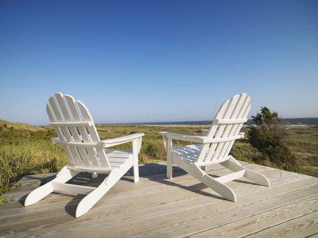 strandstoel: Twee Adirondack stoelen op houten dek met uitzicht op strand bij Bald Head Island, North Carolina.