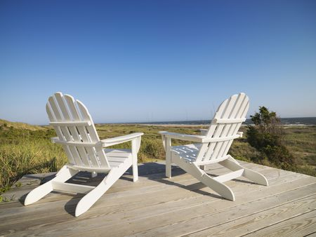 bald head: Two adirondack chairs on wooden deck overlooking beach at Bald Head Island, North Carolina.