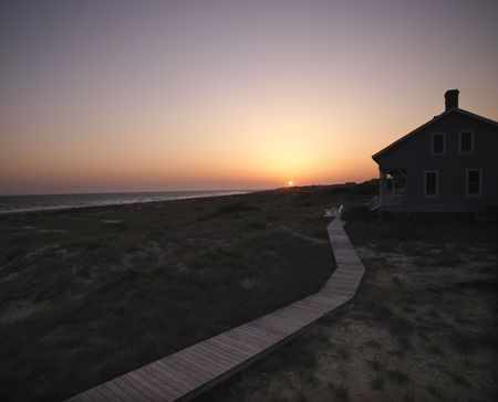 bald head: Sunset over coastal beach house with wooden boardwalk at  Bald Head Island, North Carolina.