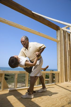African American middle aged couple dancing in new home construction at beach. photo