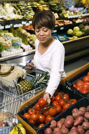 Middle aged African American woman selecting tomatoes from grocery store produce.
