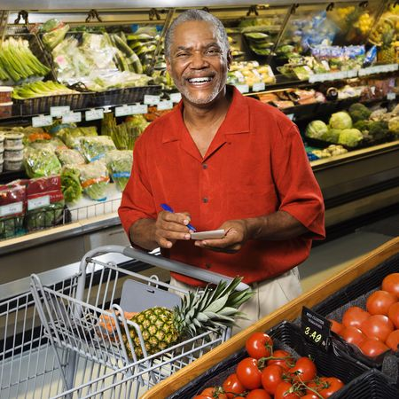 Middle aged African American man in grocery store holding shopping list and smiling at viewer. photo