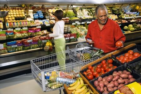 tiendas de comida: Hombre y mujer americanos africanos envejecidos centro en las compras del almac�n de la tienda de comestibles para el producto. Foto de archivo