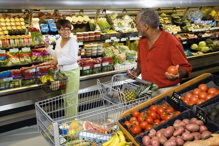 Middle aged African American woman pointing out produce in grocery store to middle aged man.