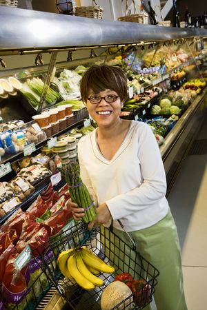 smilling: Middle aged African American woman in grocery store holding produce smilling at viewer. Stock Photo