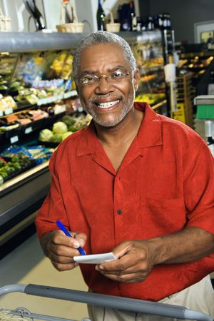 half length posed: Middle aged African American man in grocery store holding shopping list and smiling at viewer. Stock Photo