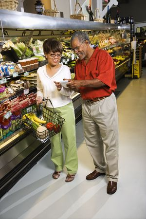 Middle aged African American couple in grocery store pointing at shopping list and smiling. photo