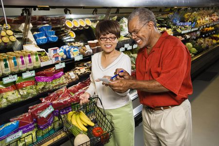 groceries shopping: Middle aged African American man and woman in grocery store smiling and pointing at shopping list. Stock Photo