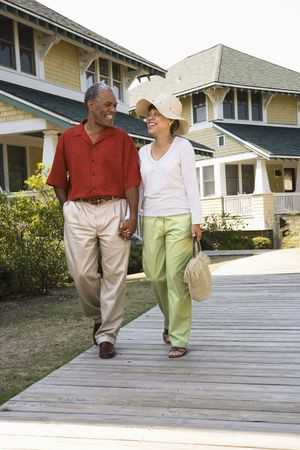 African American middle aged couple holding hands strolling on wooden walkway. Stock Photo - 2044446