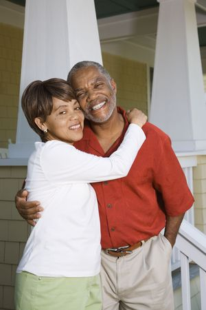 half length posed: African American middle aged couple hugging and smiling at viewer.