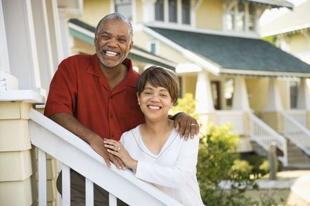 half length posed: African American middle aged couple standing together on stairs outside home.