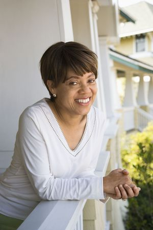 middle aged woman smiling: African American middle aged woman smiling at viewer and leaning on porch railing. Stock Photo