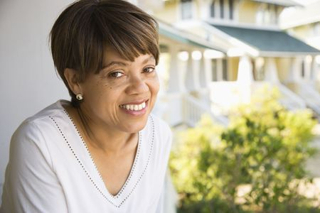 African American middle aged woman smiling at viewer outside home. Stock Photo