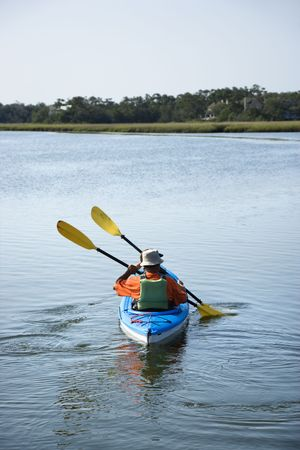 boater: Back view of African American middle-aged couple paddling kayak.