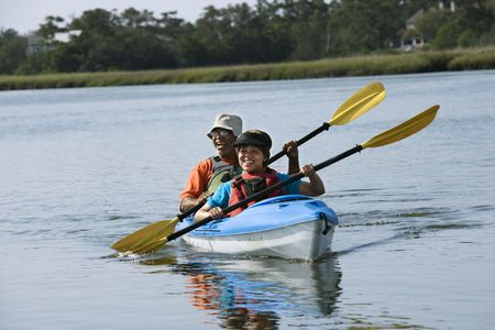 boater: African American middle-aged couple smiling and paddling kayak.