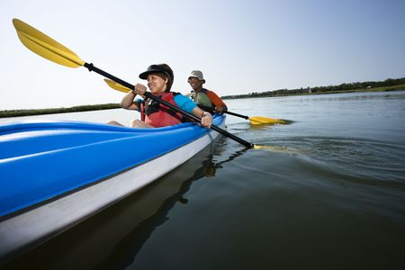 boater: Low angle of African American middle-aged man and woman paddling kayak.