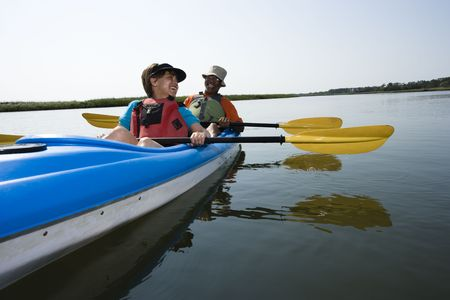 boater: African American middle-aged couple sitting in kayak on lake smiling and laughing.